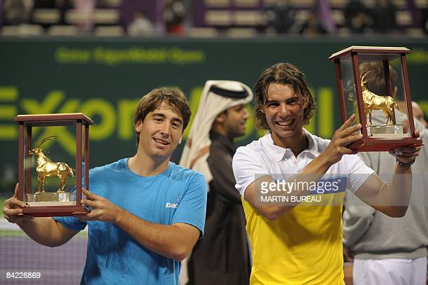 Spanish players Marc Lopez and Rafael Nadal hold up their trophies on January 9 2009 in Doha after they won the doubles final against Canadian Daniel...