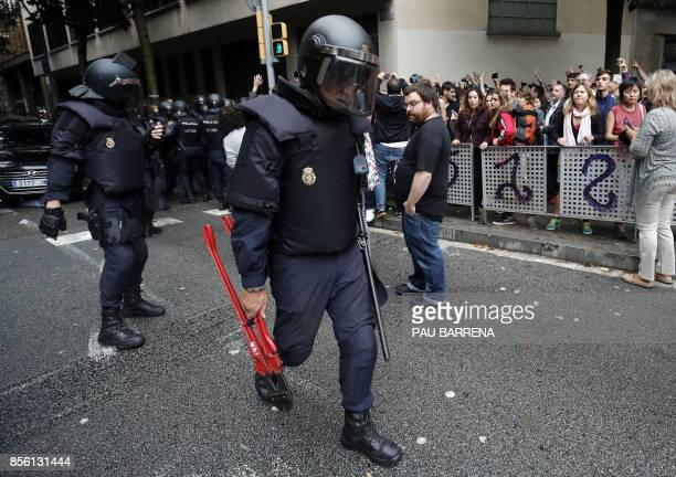 A Spanish police officer carry pliers after seizing ballotboxes in a polling station in Barcelona on October 1 on the day of a referendum on...