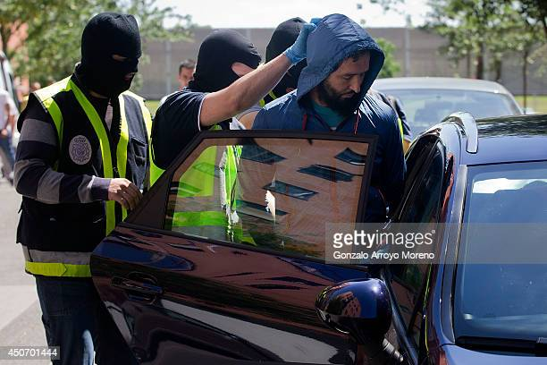 Spanish police officers arrest a man suspected of belonging to an international Jihadist recruiting network at Rutilo street on June 16 2014 in...