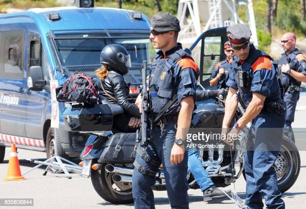 Spanish police officers control vehicles as they cross the SpanishFrench border between LaJonquera northern Spain and LePerthus southern France on...