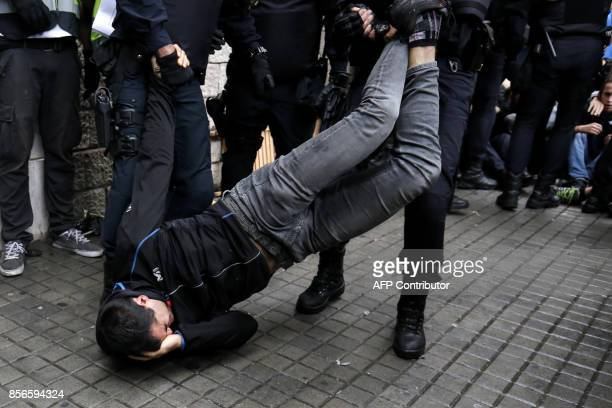 Spanish police officers drag a man as they try to disperse voters arriving to a polling station in Barcelona on October 1 2017 during a referendum on...