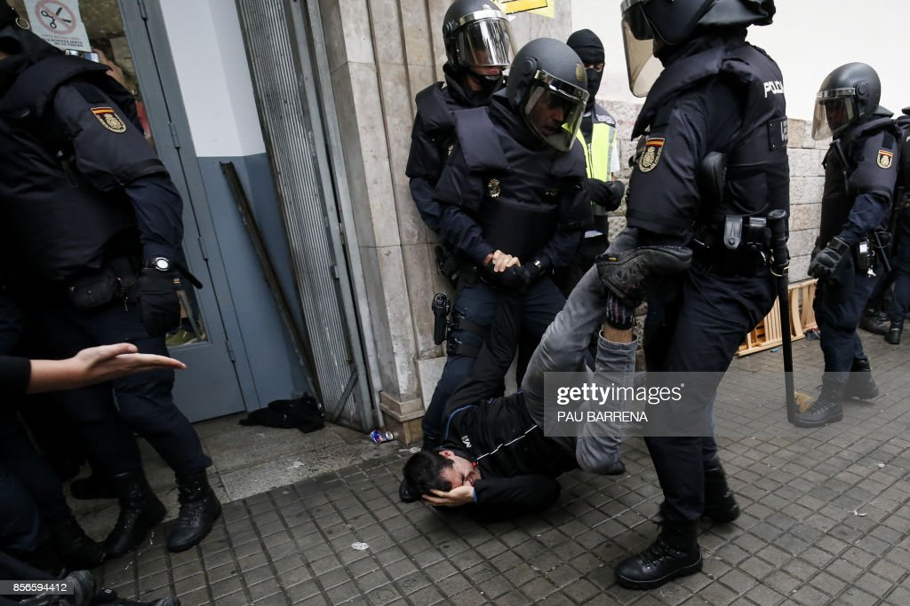 TOPSHOT - Spanish police officers drag a man as they try to disperse voters arriving to a polling station in Barcelona, on October 1, 2017 during a referendum on independence for Catalonia banned by Madrid. /