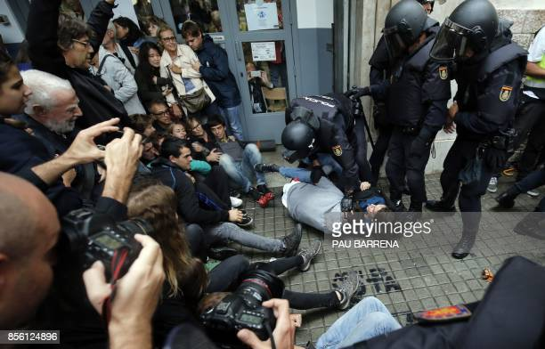 TOPSHOT Spanish police officers immobilize some people outside a polling station in Barcelona on October 1 on the day of a referendum on independence...