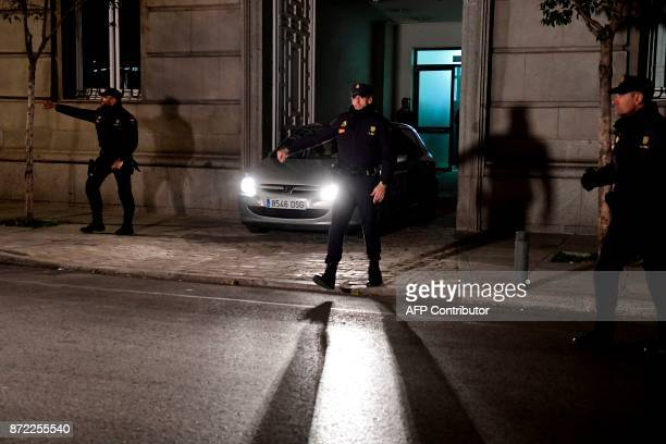Spanish police officers stand guard as a police vehicle carrying the former speaker of Catalonia's dissolved regional parliament Carme Forcadell...