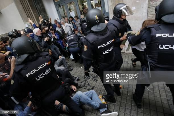 Spanish police officers try to disperse voters arriving to a polling station in Barcelona on October 1 2017 during a referendum on independence for...