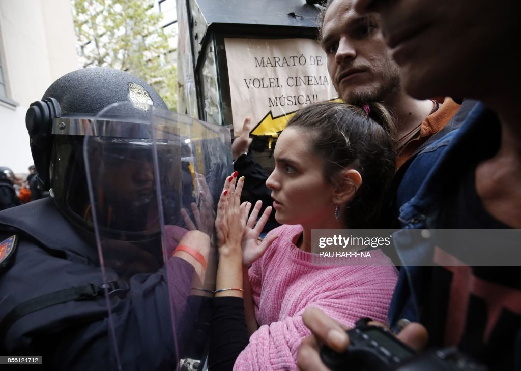 TOPSHOT - Spanish police push people with a shield outside a polling station in Barcelona, on October 1, 2017, on the day of a referendum on independence for Catalonia banned by Madrid. More than 5.3 million Catalans are called today to vote in a referendum on independence, surrounded by uncertainty over the intention of Spanish institutions to prevent this plebiscite banned by justice. BARRENA