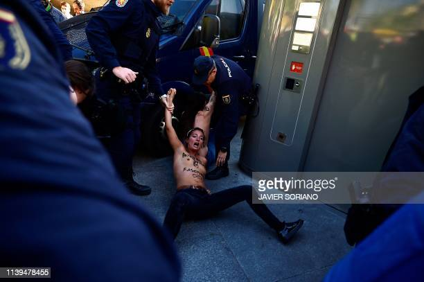 Spanish police stop an activist from the women's rights organisation Femen as they disperse a protest before the start of Spanish farright party...
