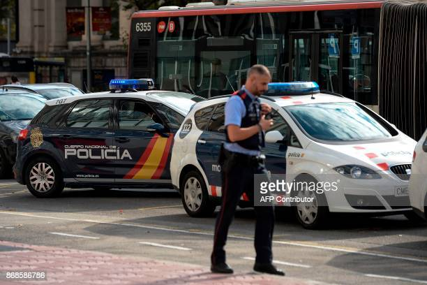 A Spanish police vehicle is parked next to a car of the Catalan regional police force Mossos d'Esquadra outside the Catalan police headquarters in...