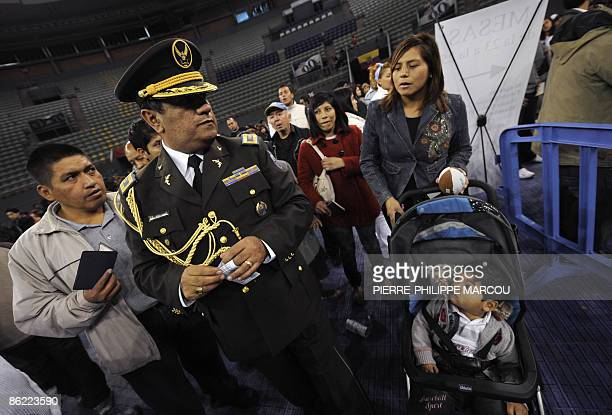 A Spanish policeman assists Ecuadorian citizens living in Spain during an overseas voting session for the presidential election at a pollingstation...