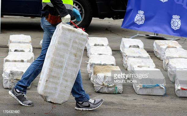 A Spanish policeman removes a bag of packs of cocaine seized on the vessel Riptide at the port of Vigo northwestern Spain on June 13 2013 Spanish...
