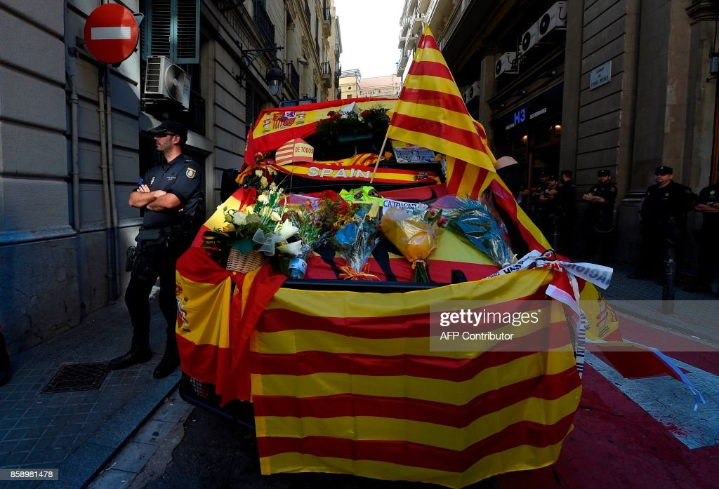 Spanish policeman stands next to a police van decorated with Spanish and Catalan flags by protesters attending a demonstration called by 'Societat Civil Catalana' (Catalan Civil Society) to support the unity of Spain on October 8, 2017 in Barcelona. Ten of thousands of flag-waving demonstrators packed central Barcelona to rally against plans by separatist leaders to declare Catalonia independent following a banned secession referendum. Catalans calling themselves a 'silent majority' opposed to leaving Spain broke their silence after a week of mounting anxiety over the country's worst political crisis in a generation. /