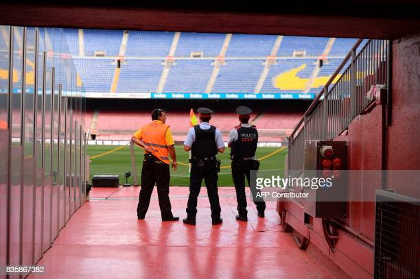Spanish policemen and a security member of the Camp Nou stadium chat before the Spanish league footbal match FC Barcelona vs Real Betis at the Camp...