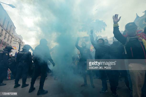 Spanish policemen and civil guards sporting Guy Fawkes masks protest in front of Spanish policemen standing guard during a demonstration to demand...