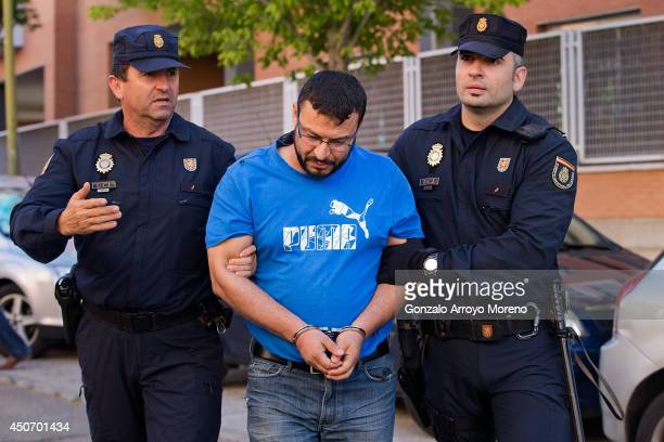 Spanish policemen arrest a man suspected of belonging to an international Jihadist recruiting network at Brujas street on June 16 2014 in Madrid...