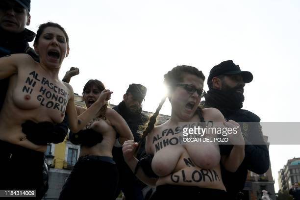 Spanish policemen restrain members of the feminist movement Femen as they protest against a far right demonstration marking the anniversary of the...