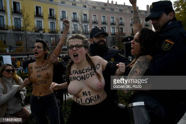 TOPSHOT Spanish policemen restrain members of the feminist movement Femen as they protest against a far right demonstration marking the anniversary...