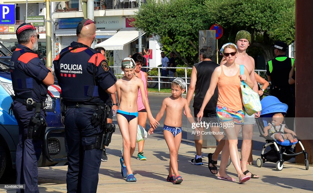 Spanish policemen stand guard as tourists pass by in Cambrils on August 18, 2017, a day after a van ploughed into the crowd, killing 13 persons and injuring over 100 on the Rambla in Barcelona. Drivers have ploughed on August 17, 2017 into pedestrians in two quick-succession, separate attacks in Barcelona and another popular Spanish seaside city, leaving 13 people dead and injuring more than 100 others. In the first incident, which was claimed by the Islamic State group, a white van sped into a street packed full of tourists in central Barcelona on Thursday afternoon, knocking people out of the way and killing 13 in a scene of chaos and horror. Some eight hours later in Cambrils, a city 120 kilometres south of Barcelona, an Audi A3 car rammed into pedestrians, injuring six civilians -- one of them critical -- and a police officer, authorities said. /