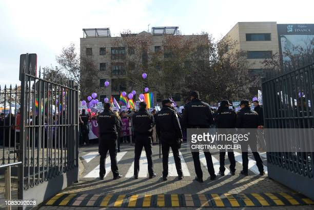 Spanish policemen stand guard as women demonstrate against the farright party VOX on January 15 2019 in front of Andalusia's regional parliament in...