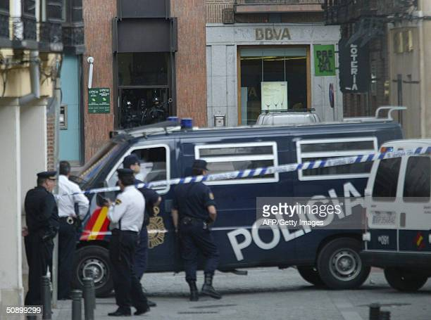 Spanish policemen stand guard in front of a bank of the brand BBVA where a Roumanian immigrant man keeps two people as hostages in Alcala de Henares...