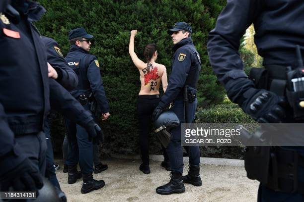 Spanish policemen surround a member of the feminist movement Femen as she protests against a far right demonstration marking the anniversary of the...
