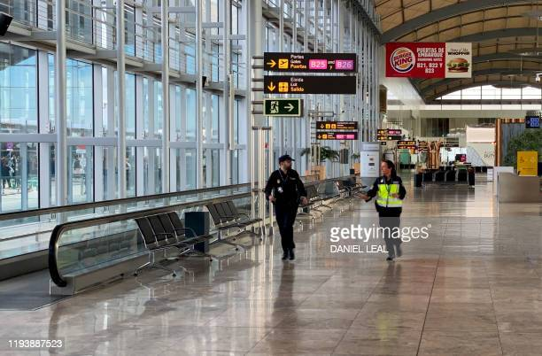 Spanish policemen walk at AlicanteElche airport on January 15 2020 in Alicante after a fire erupted in the terminal