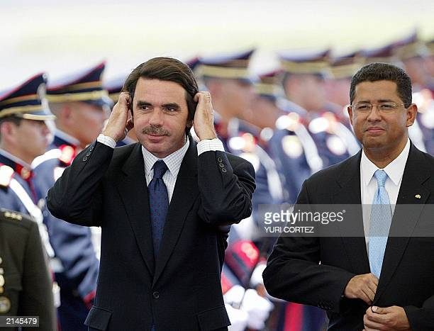 Spanish President of the Government Jose Maria Aznar puts in order his hair beside the salvadorean President Francisco Flores on July 08 2003 during...