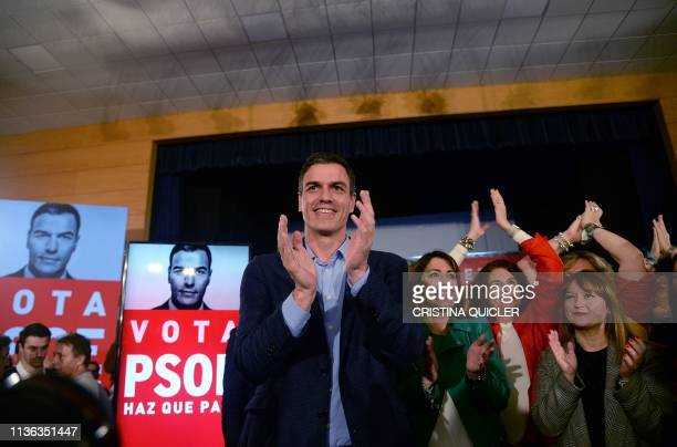 Spanish Prime Minister and candidate for prime minister Pedro Sanchez applauds after presenting his campaign poster during a rally to officially...