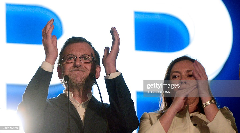 Spanish Prime Minister and Popular Party (PP) leader and candidate for general election, Mariano Rajoy (L) applauds next to his wife Elvira Fernandez (R) at the party's headquarters after the results of Spain's general elections in Madrid on December 20, 2015. Spain's ruling conservative Popular Party won the most seats in parliament in a general election Sunday but lost its absolute majority, partial results showed with over 80 percent of votes counted.