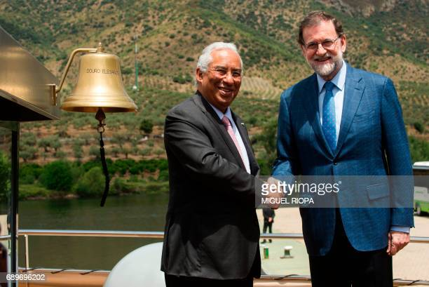 """Spanish Prime Minister Mariano Rajoy and his Portuguese counterpart Antonio Costa shake hands as they pose on the """"MS Douro Elegance"""" ship on the..."""