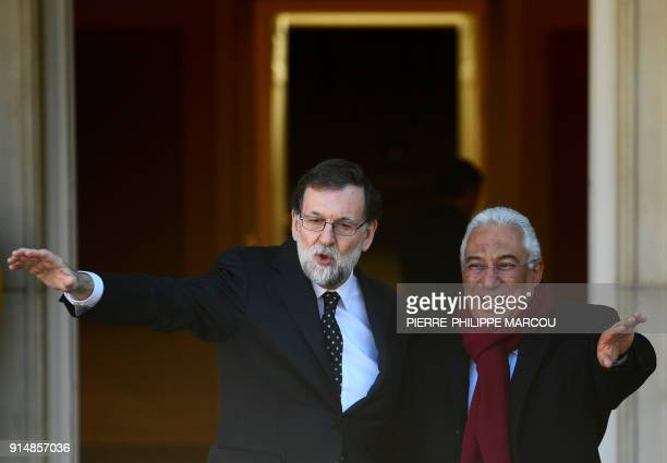 Spanish Prime minister Mariano Rajoy and his Portuguese counterpart Antonio Costa wave before holding a meeting at 'La Moncloa' palace in Madrid on...