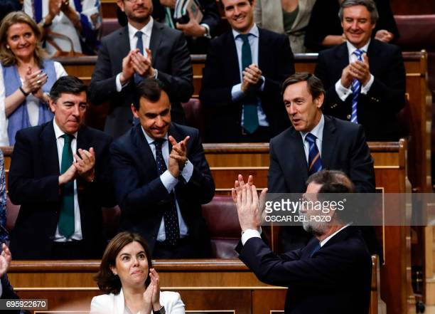 Spanish Prime Minister Mariano Rajoy applaudes as he is applauded by his party fellows at the Congress of Deputies in Madrid on June 14 2017 after a...