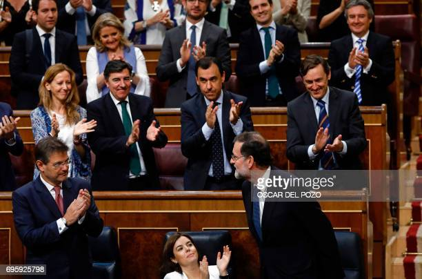 Spanish Prime Minister Mariano Rajoy is applauded by his party fellows at the Congress of Deputies in Madrid on June 14 2017 after a vote of no...