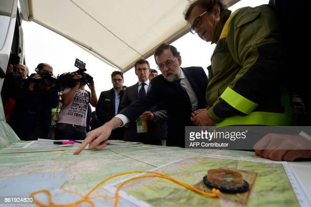 Spanish Prime Minister Mariano Rajoy points at a map of the region during a meeting with firemen at a control point in Pazos de Borben near Redondela...