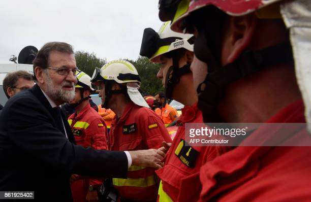Spanish Prime Minister Mariano Rajoy shakes hands with to members of the UME at a control point in Pazos de Borben near Redondela northwestern Spain...