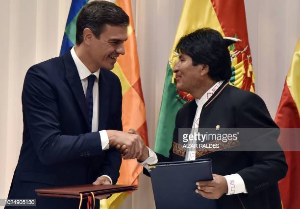 Spanish Prime Minister Pedro Sanchez and Bolivian President Evo Morales shake hands after signing bilateral agreements during a ceremony in Santa...