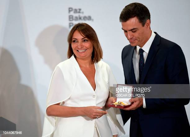 Spanish Prime Minister Pedro Sanchez gives a medal to former liaison judge between France and Spain Helene Davo recognizing her merits in the fight...