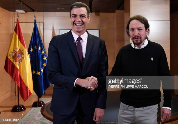 Spanish prime minister Pedro Sanchez smiles as he shakes hands with the leader of Podemos party Pablo Iglesias prior to holding a meeting at Las...