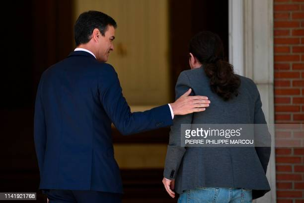Spanish prime minister Pedro Sanchez welcomes the leader of Podemos party Pablo Iglesias prior to holding a meeting at the Moncloa Palace in Madrid...