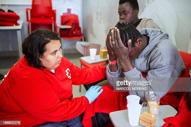 A Spanish Red Cross volunteer comforts a wouldbe immigrant after he heard of the death of one of his companions at Tarifa's harbour on April 17 2013...