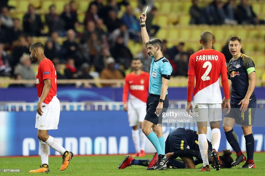 Spanish referee Alberto Undiano Mallenco (R) gives a yellow card to Monaco's Brazilian defender Jorge (L) during the UEFA Champions League group G football match between Monaco and Leipzig at the Louis II stadium, in Monaco, on November 21, 2017. / AFP PHOTO / Valery HACHE