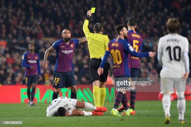 Spanish referee Antonio Mateu Lahoz shows a yellow card to Barcelona's Chilean midfielder Arturo Vidal during the Spanish Copa del Rey semifinal...