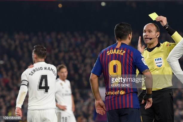 Spanish referee Antonio Mateu Lahoz shows a yellow card to Barcelona's Uruguayan forward Luis Suarez during the Spanish Copa del Rey semifinal first...