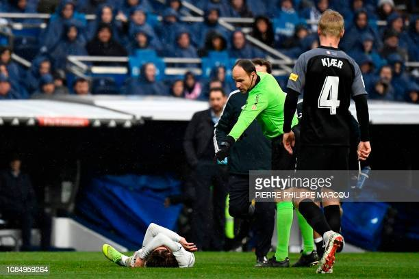 Spanish referee Antonio Miguel Mateu Lahoz gestures as Real Madrid's Croatian midfielder Luka Modric lies on the ground after being injured during...
