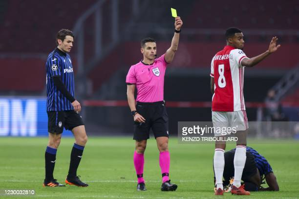 Spanish referee Carlos Del Cerro Grande gives a yellow card to Ajax's Dutch midfielder Ryan Gravenberch during the UEFA Champions League Group D...