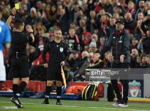 Spanish referee Carlos del Cerro Grande shows a yellow card to Liverpool's German manager Jurgen Klopp during the UEFA Champions league Group E...