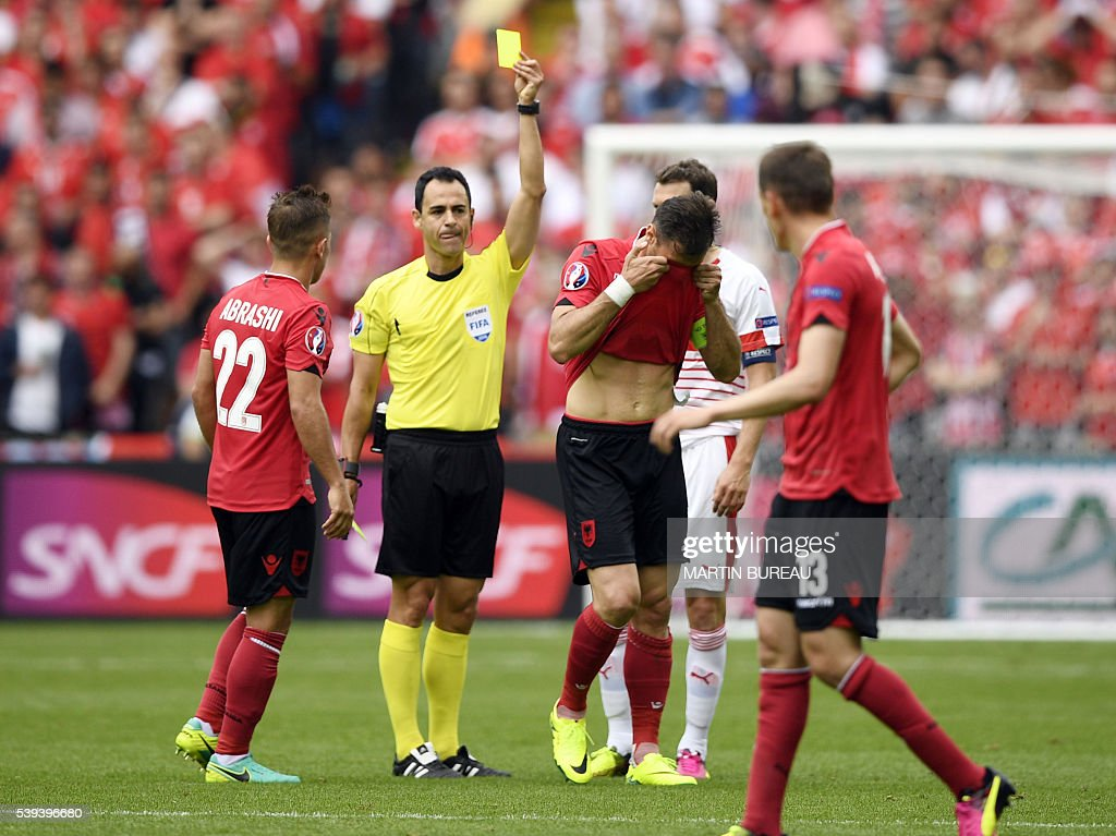 Spanish referee Carlos Velasco (2nd L) shows a yellow card to Albania's defender Lorik Cana (C) during the Euro 2016 group A football match between Albania and Switzerland at the Bollaert-Delelis Stadium in Lens on June 11, 2016. / AFP / MARTIN
