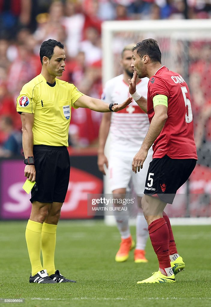 Spanish referee Carlos Velasco (L) speaks with Albania's defender Lorik Cana (C) during the Euro 2016 group A football match between Albania and Switzerland at the Bollaert-Delelis Stadium in Lens on June 11, 2016. / AFP / MARTIN