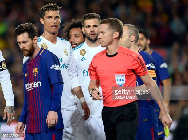 Spanish referee Hernandez Hernandez walks past Barcelona's Argentinian forward Lionel Messi and Real Madrid's Portuguese forward Cristiano Ronaldo...