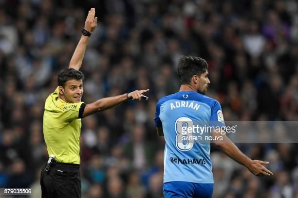 Spanish referee Jesus Gil Manzano gestures next to Malaga's Spanish midfielder Adrian Gonzalez Morales during the Spanish league football match Real...