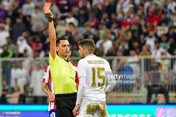 Spanish referee Jose Maria Sanchez Martinez presents a red card to Real Madrid's Uruguayan midfielder Federico Valverde during the Spanish Super Cup...